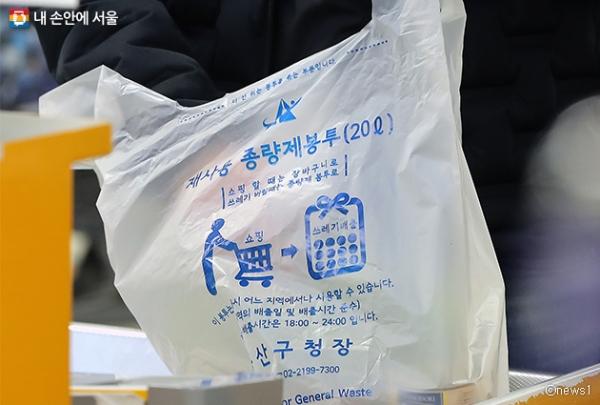 서울의 한 대형마트에서 한 시민이 계산을 마친 물품을 종량제 봉투에 담고 있다